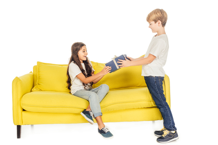 boy presenting gift box to friend on yellow sofa isolated on white Stock Photo