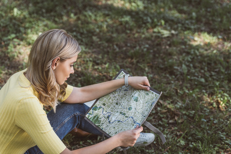 young tourist looking for destination on map in park Imagens