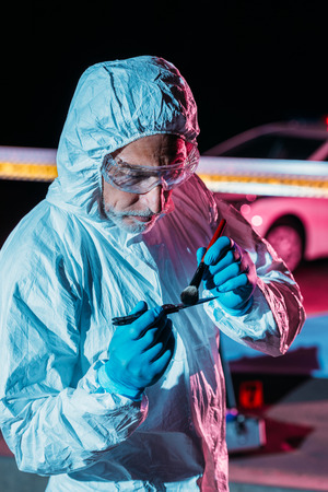 male criminologist in protective suit and latex gloves taking fingerprints from knife at crime scene