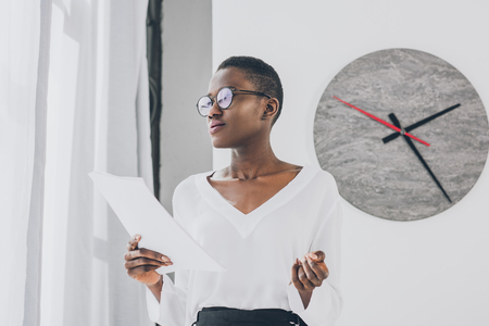 stylish attractive african american businesswoman holding documents and looking away in office