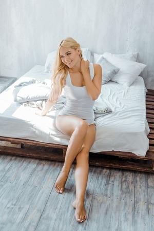 vue grand angle de belle fille souriante en sous-vêtements assis sur le lit et à l'écart