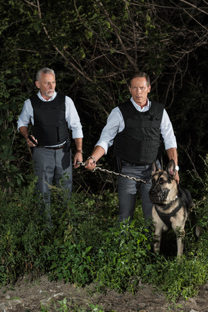 male police officers in bulletproof vests with german shepherd dog on leash near forest