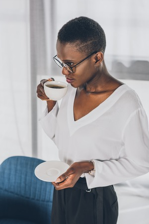 stylish attractive african american businesswoman drinking coffee in office