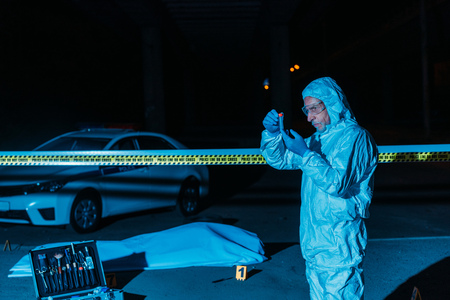 mature male criminologist in protective suit and latex gloves collecting evidence at crime scene with corpse