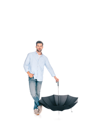 full length view of handsome man holding black umbrella and looking at camera isolated on white Standard-Bild - 111854579