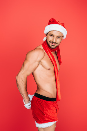 sexy muscular shirtless man in christmas hat and red scarf posing isolated on red background Stock Photo