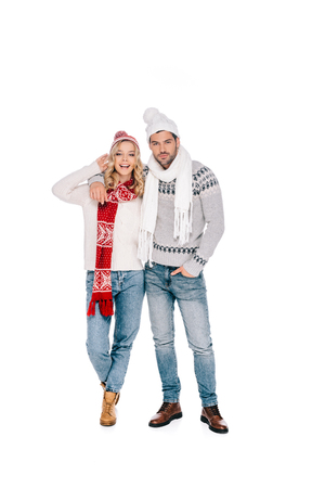 beautiful happy young couple in sweaters, scarves and hats standing together and looking at camera isolated on white Stockfoto - 112245861