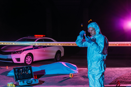 middle aged male criminologist in protective suit and latex gloves collecting evidence at crime scene with corpse Zdjęcie Seryjne