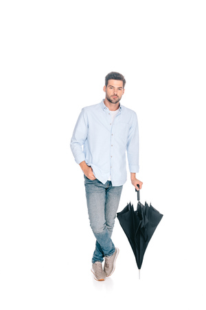 handsome man holding black umbrella and looking at camera isolated on white Standard-Bild - 112245942