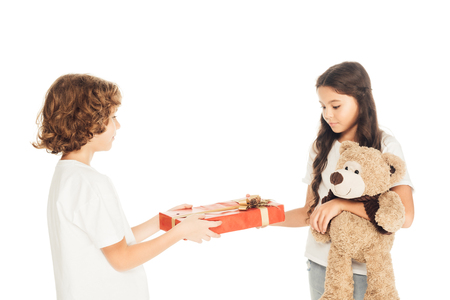 side view of boy presenting gift box to friend isolated on white