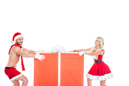 happy couple in christmas clothes pulling big gift box in different directions isolated on white background Stock Photo