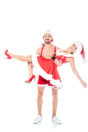 handsome muscular shirtless man in christmas hat holding girlfriend on hands isolated on white background