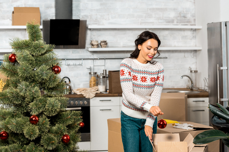 happy young woman decorating christmas tree by baubles in kitchen at home Stock Photo