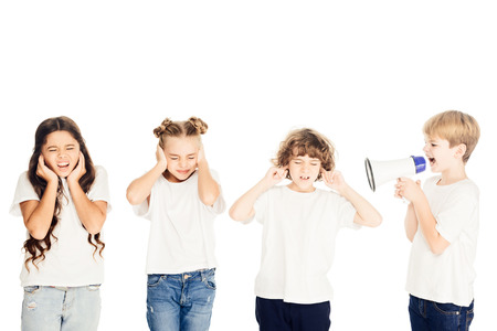 boy screaming in megaphone, kids covering ears isolated on white Stock Photo