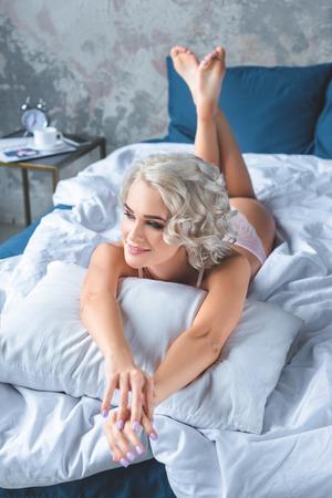 happy young woman lying on bed in underwear Standard-Bild - 112246132