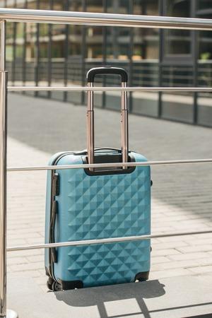 light blue travel bag near railing on street