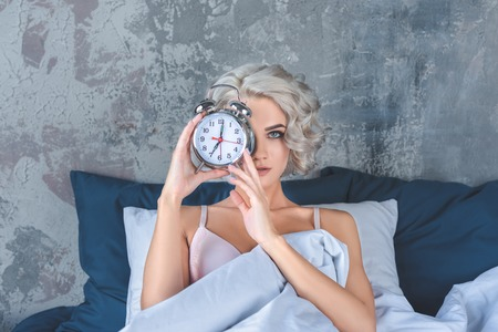 attractive young woman lying in bed and covering half of face with alarm clock