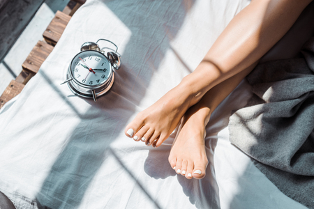 partial top view of female feet and alarm clock on bed Stok Fotoğraf