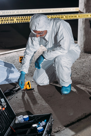 male criminologist in protective suit and latex gloves collecting evidence at crime scene with corpse Stock Photo