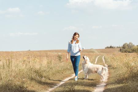 beautiful adult woman walking by field with retriever dog Stock fotó