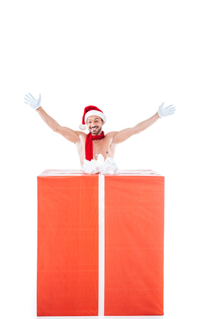 happy shirtless muscular man in christmas hat standing with raised arms near big gift box isolated on white background Stock Photo