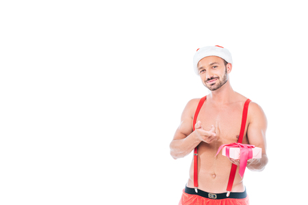 happy shirtless muscular man in christmas hat pointing at gift box isolated on white background