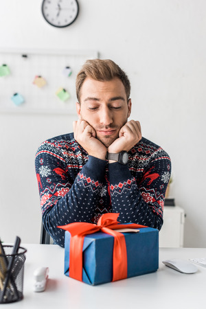 thoughtful businessman in christmas sweater looking at gift box in office Stock Photo