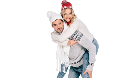 beautiful happy young couple in sweaters, scarves and hats piggybacking and smiling at camera isolated on white Stock Photo