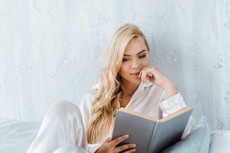 focused young woman in pajamas sitting on bed and reading book