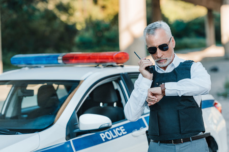 middle aged policeman in bulletproof vest and sunglasses checking wristwatch near car at street