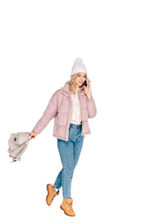beautiful smiling young woman holding backpack and talking by smartphone isolated on white Stockfoto
