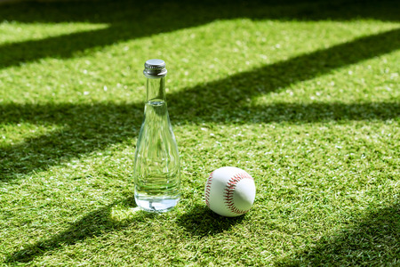 glass water battle with baseball ball lying on green grass Banco de Imagens