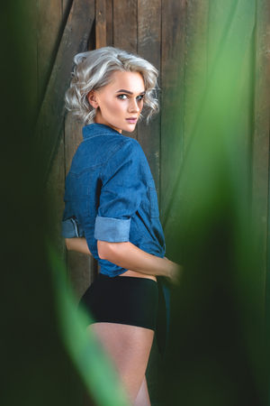 attractive young woman in denim shirt and underwear looking at camera through plant leaves Standard-Bild - 111231734