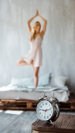 close-up view of alarm clock on wooden table and young woman performing yoga on bed behind