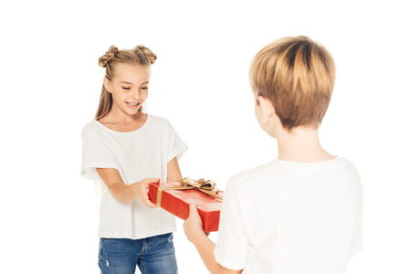 boy presenting gift box to happy friend isolated on white