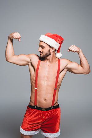 muscular man in christmas hat showing muscles isolated on grey background