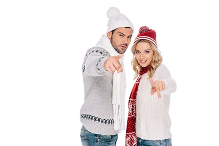 beautiful young couple in winter outfit standing together and pointing at camera isolated on white