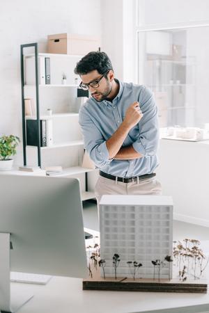 Gut aussehender Architekt, der Computer in der Nähe des Architekturmodells auf dem Tisch im Büro betrachtet