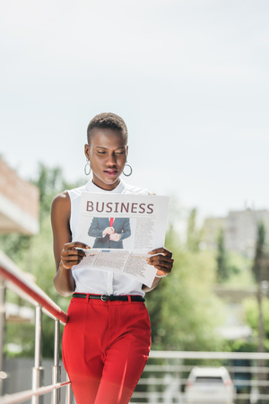 fashionable attractive african american businesswoman reading business newspaper on street