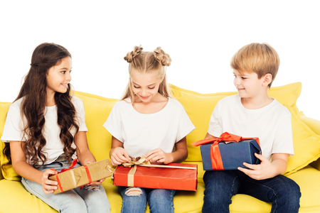 adorable kids sitting on yellow sofa and opening gift boxes isolated on white