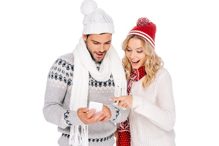 beautiful smiling young couple in sweaters, scarves and hats using smartphone isolated on white