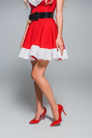 cropped image of seductive santa girl in red shoes with heels on grey background Stockfoto