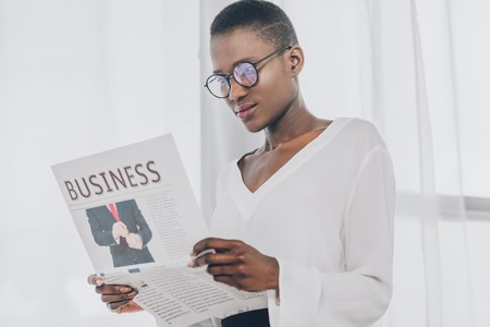 stylish attractive african american businesswoman reading newspaper in office Stock Photo