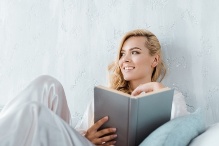 attractive smiling young woman in pajamas holding book and looking away while in bedroom Stock Photo