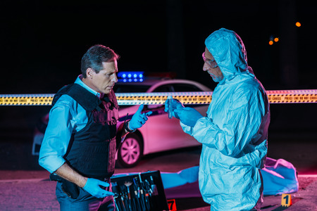 male criminologist in protecitve suit showing evidence to mature policeman at crime scene with corpse in body bag Stock Photo