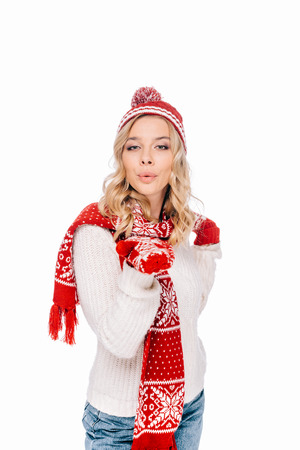 beautiful young woman in hat, scarf and mittens blowing kiss and looking at camera isolated on white