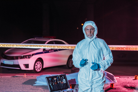 mature male criminologist in protective suit and mask looking at camera near crime scene with corpse in body bag Zdjęcie Seryjne
