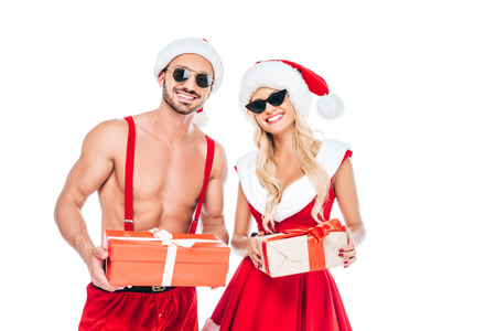 portrait of young couple in christmas hats and sunglasses holding gift boxes isolated on white background