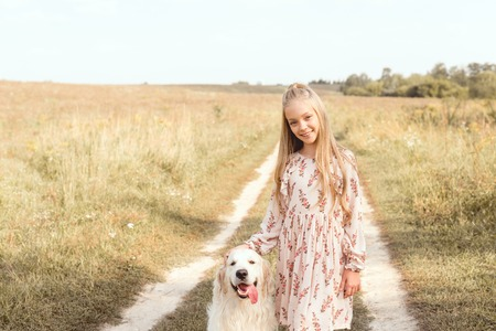 beautiful little child with adorable golden retriever dog looking at camera in field
