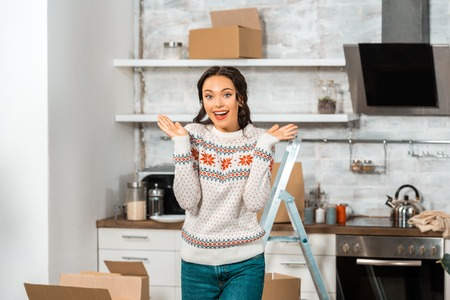 smiling young woman doing shrug gesture in kitchen during relocation in new home Stock Photo